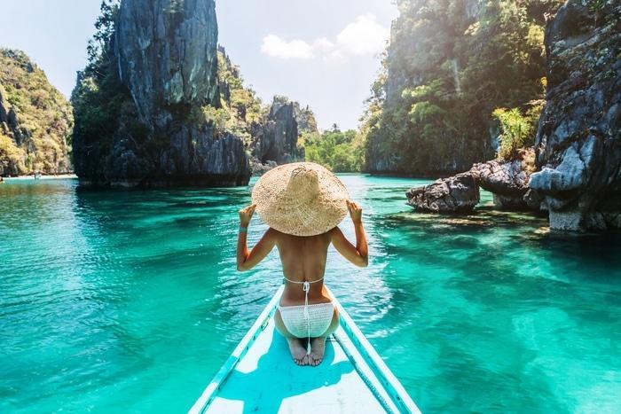 mulher com chapeu de palha num barco tradicional filipino
