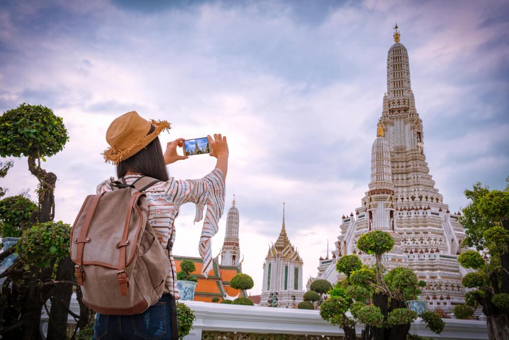 mulher tira fotos a um templo na tailandia