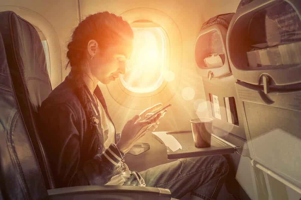 mulher a utilizar telefone no aviao