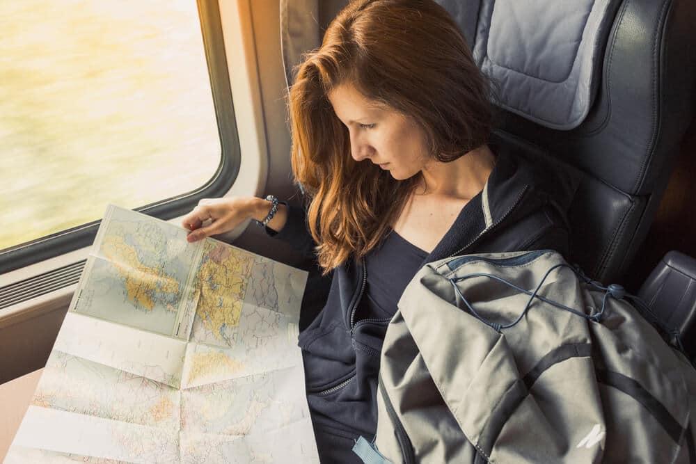mulher a consultar mapa num comboio