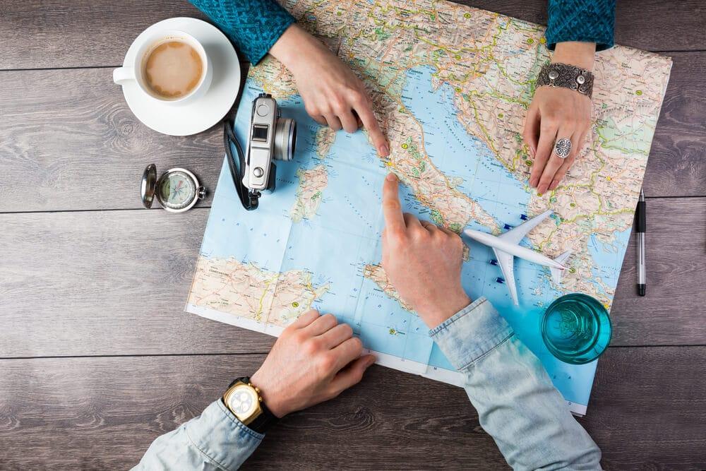 maos de duas pessoas sobre um mapa mundi