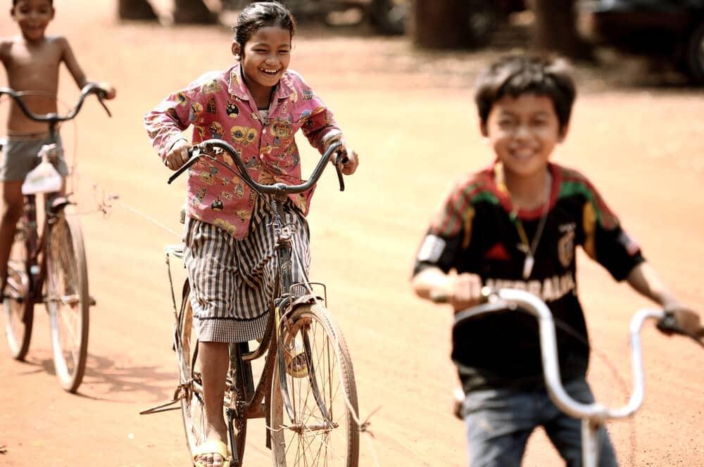 crianças andam de bicicleta em siem reap