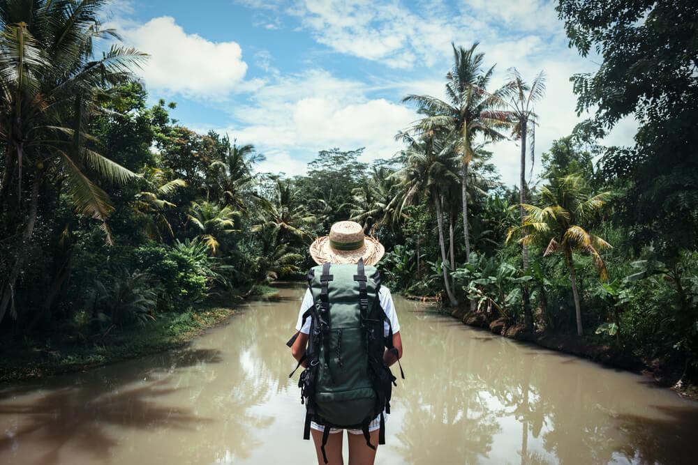 mulher com chapeu de palha olha para um rio numa floresta tropical