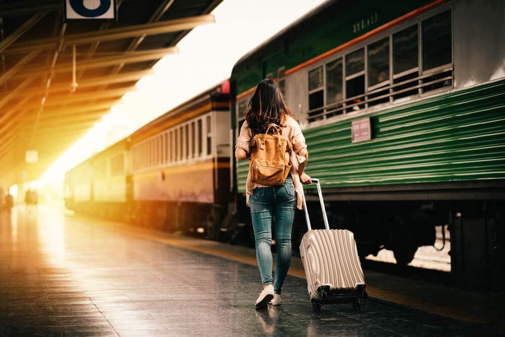 mulher viajante com mala ao lado de um comboio verde