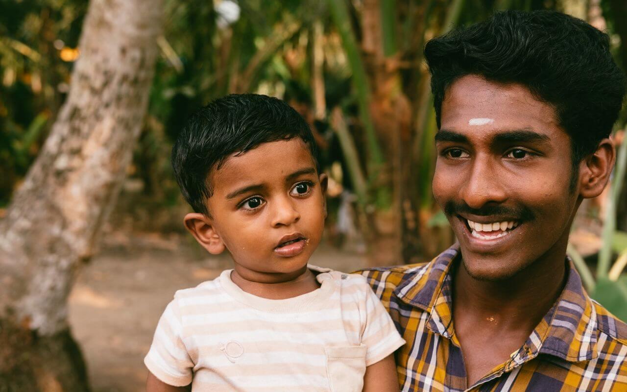pai e filho indianos sorriem para a camara