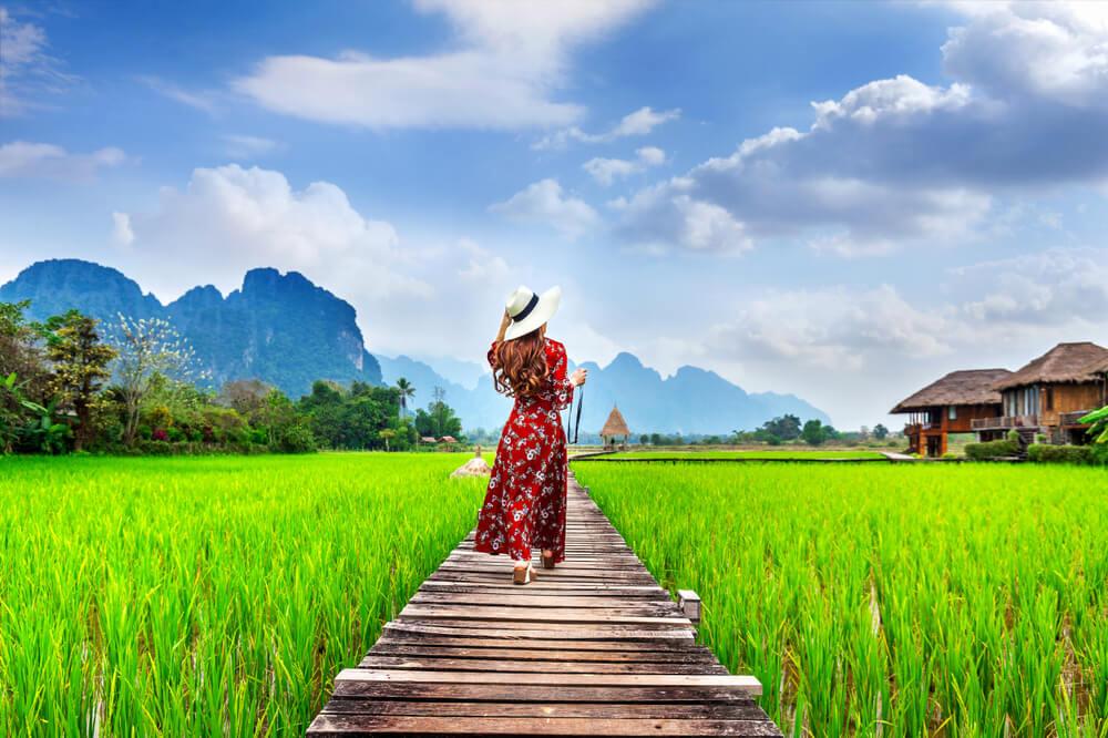 mulher com chapeu de palha passeio pelos campos de arroz