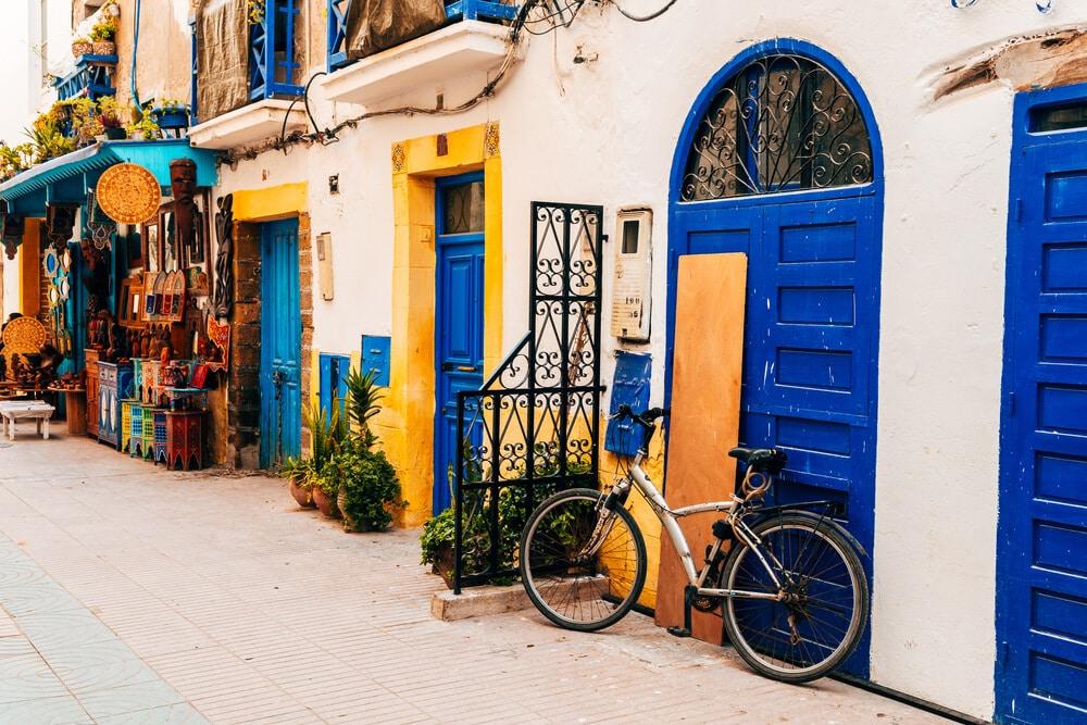 rua colorida de essaouira com bicicleta parada em frente de uma porta azul
