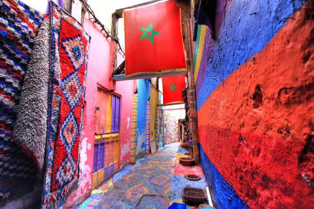 rua estreita em tons vermelhos e azuis com bandeiras de marrocos penduradas