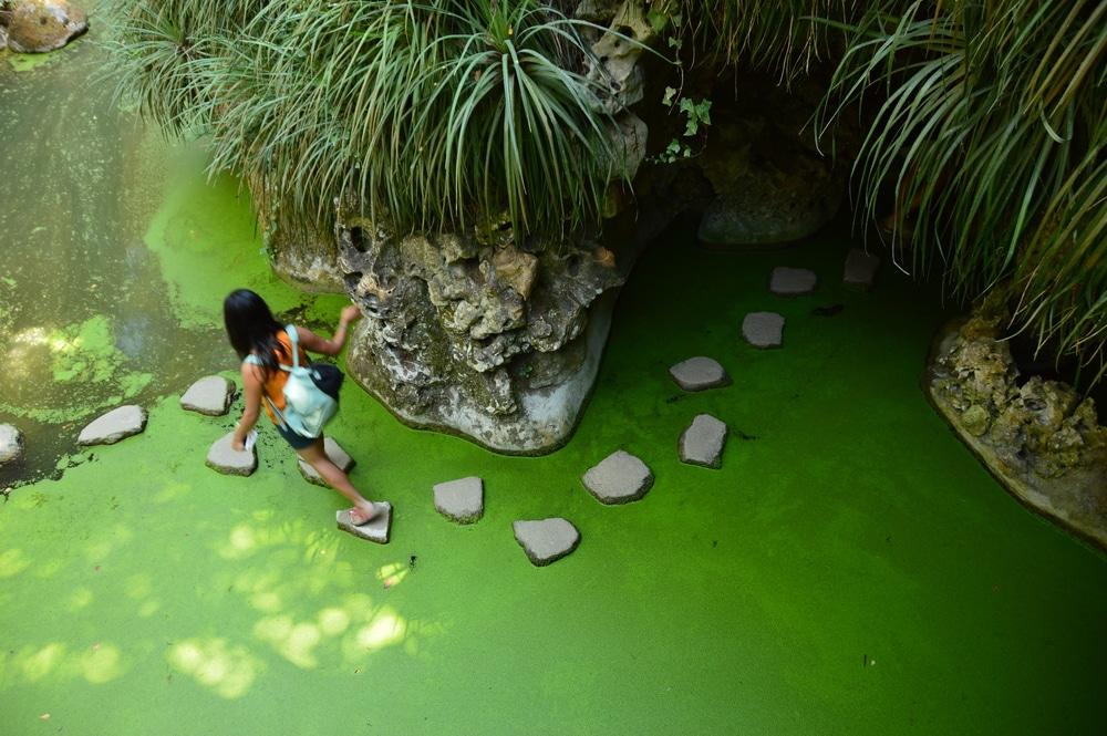 mulher jovem atravessa o lago da quinta pisando as pedras brancas