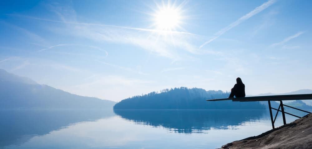 mulher sentada num cais na margem de um lago em posiçao pensativa