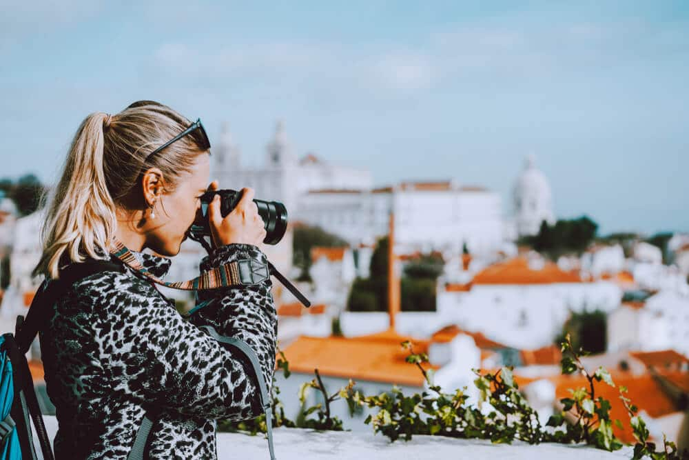 mulher a fotografar lisboa desde o miradouro das portas do sol