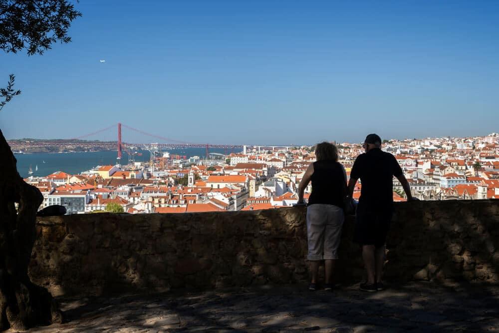casal observa lisboa desde o miradouro doo castelo de sao jorge
