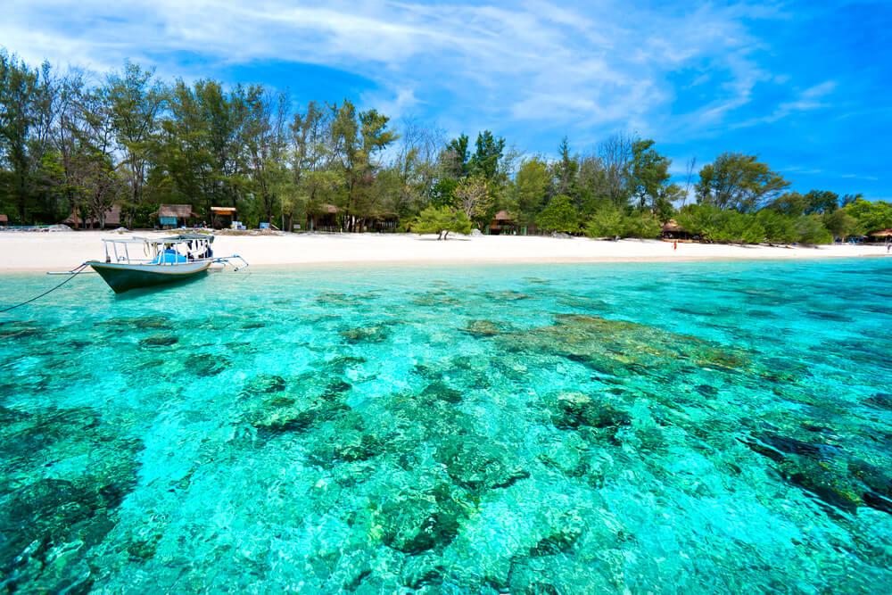 praia de gili meno com barco atracado na areia