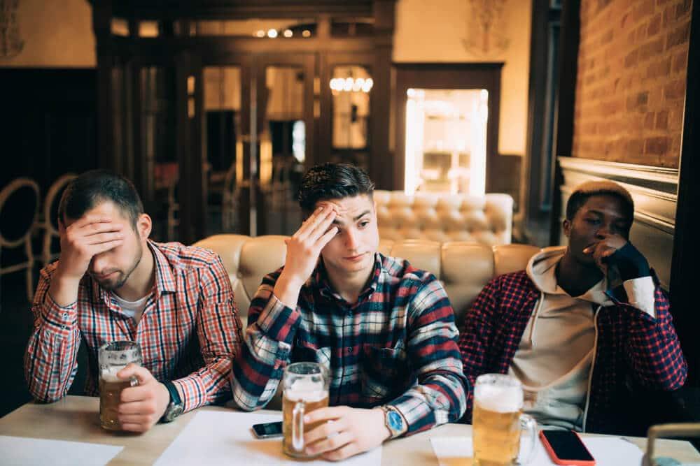 tres amigos chateados num bar com cervejas