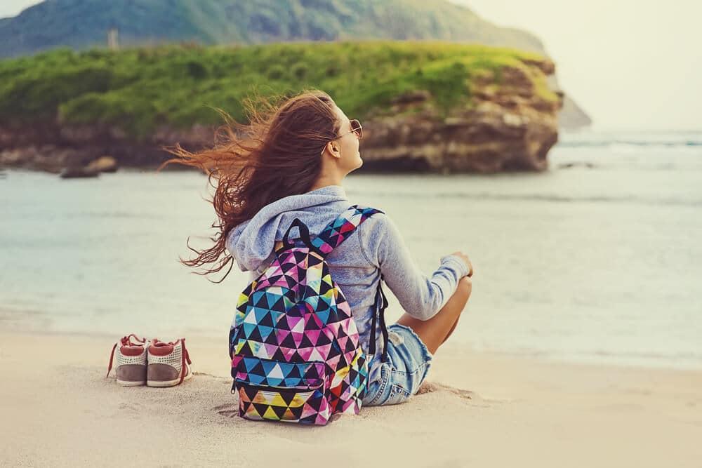 mulher desfruta sozinha sentada na praia