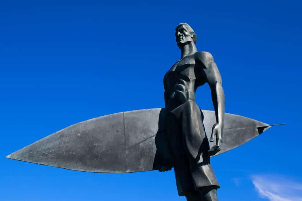 estatua dedicada ao surf em fundo de ceu azul