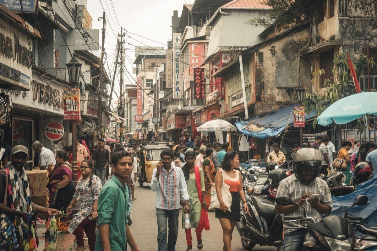 rua de kerala cheia de pessoas e postos de venda ambulante