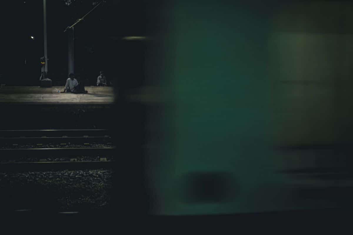 pessoa sentada à noite numa estaçao de comboios
