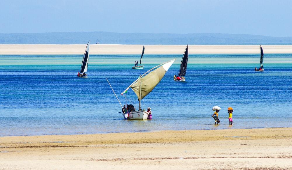 pessoas e barcos tradicionais numa praia de moçambique