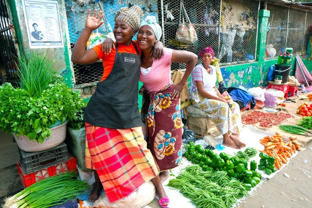 mulheres sorriem num mercado de vegetais em maputo