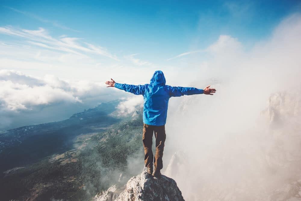 homem sozinho no cume de uma montanha tira foto de braços abertos