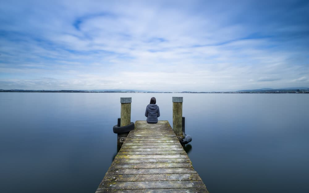 mulher sentada num cais de madeira na margem de um lago