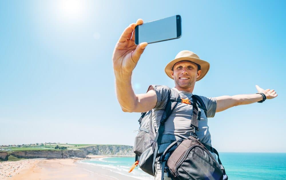homem tira selfie sozinho numa praia
