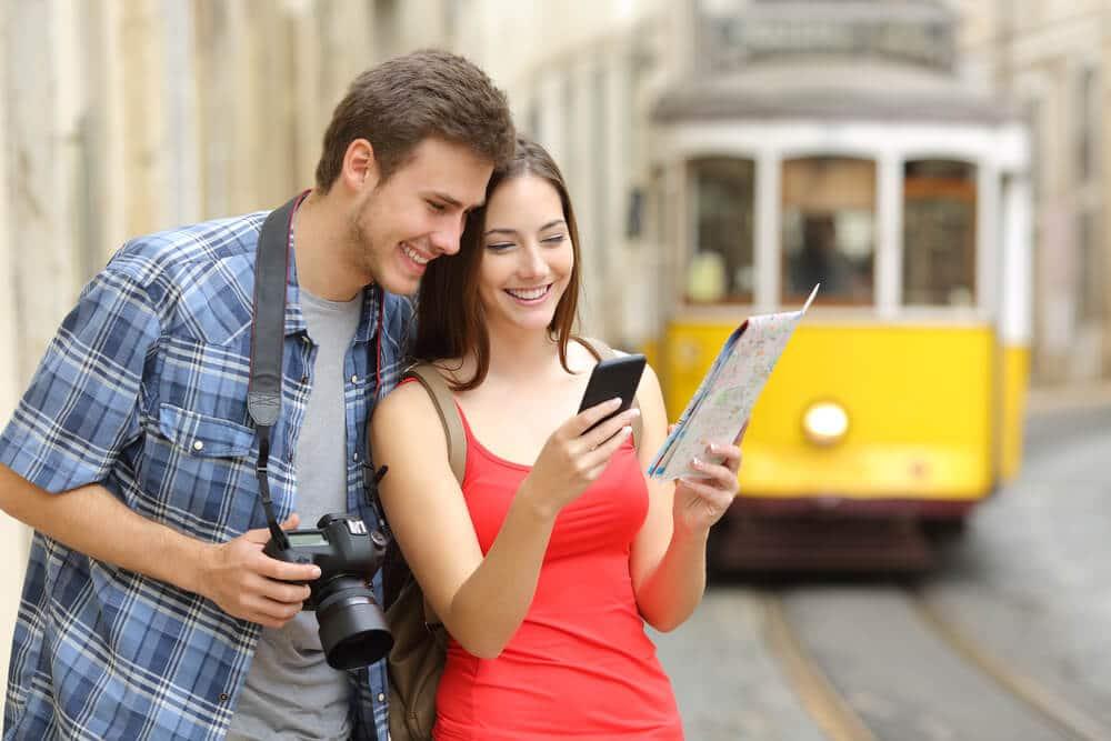 dois jovens de viagem por lisboa procuram indicaçoes num mapa e num telemovel