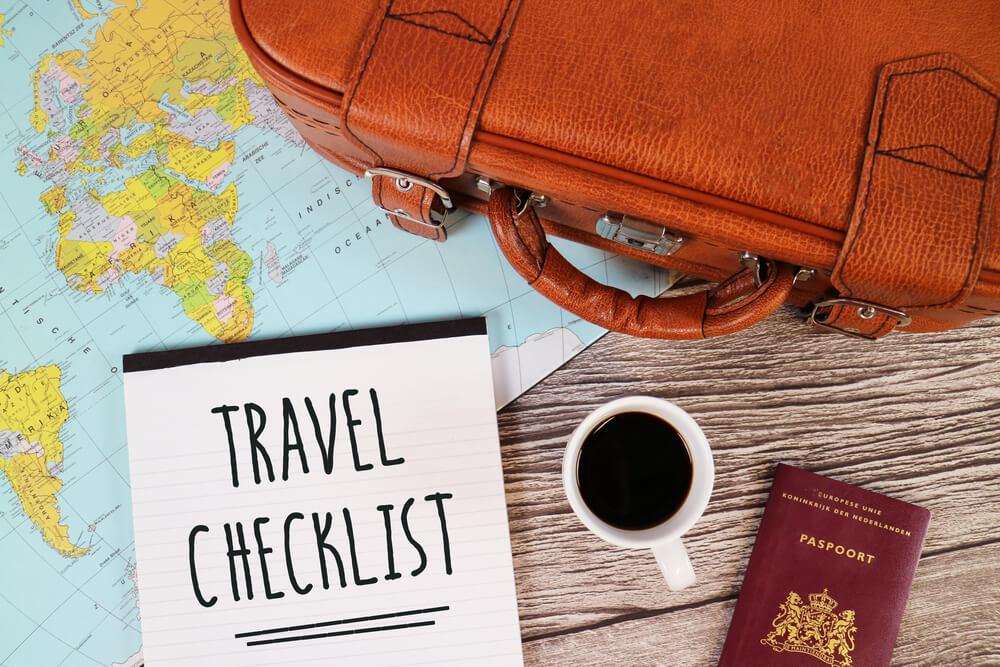 checklist, cafe e mala pousados em cima de um mapa mundo