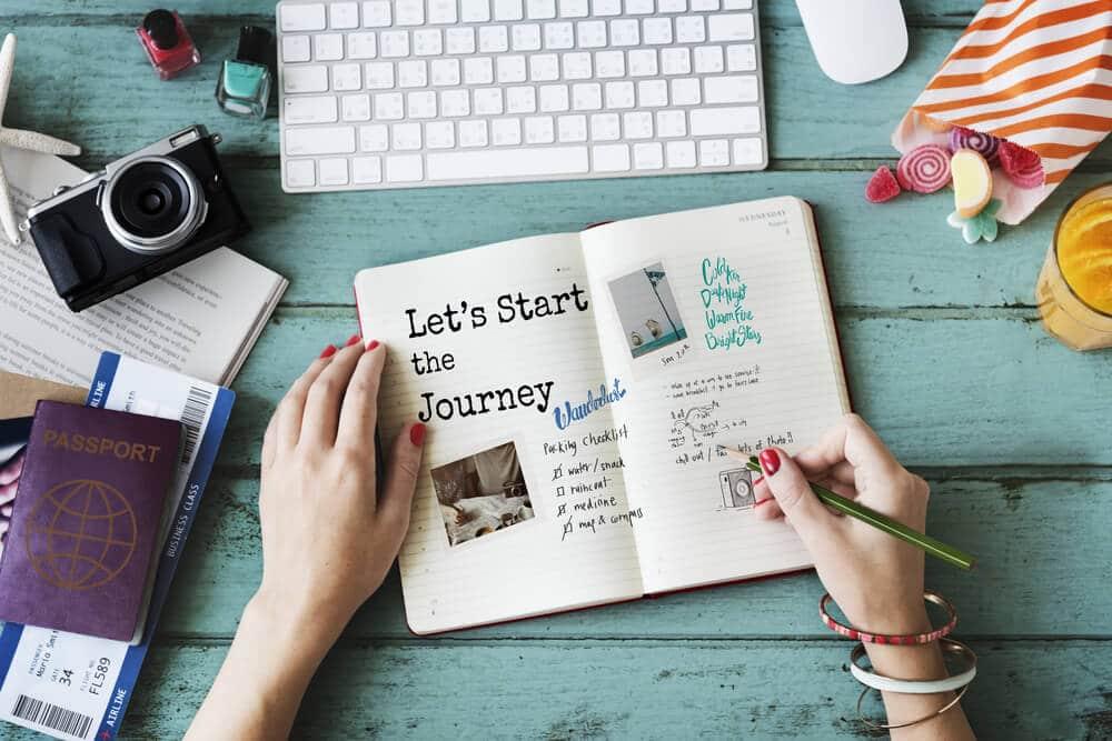 jovem escreve num diario de viagem