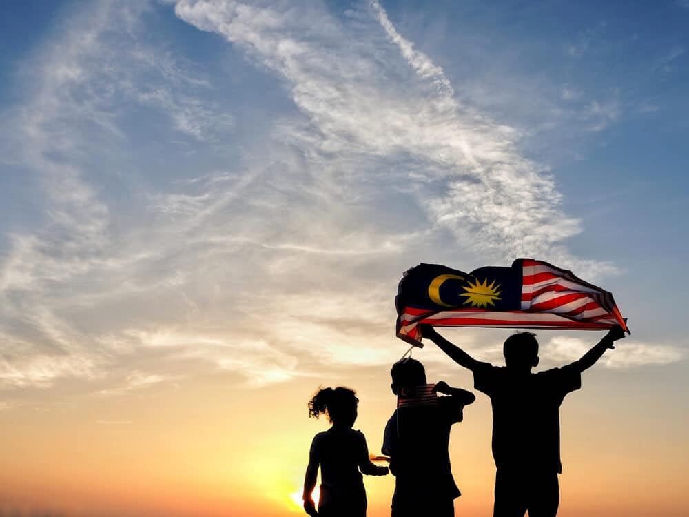 tres jovens seguram uma bandeira da malasia a contra luz