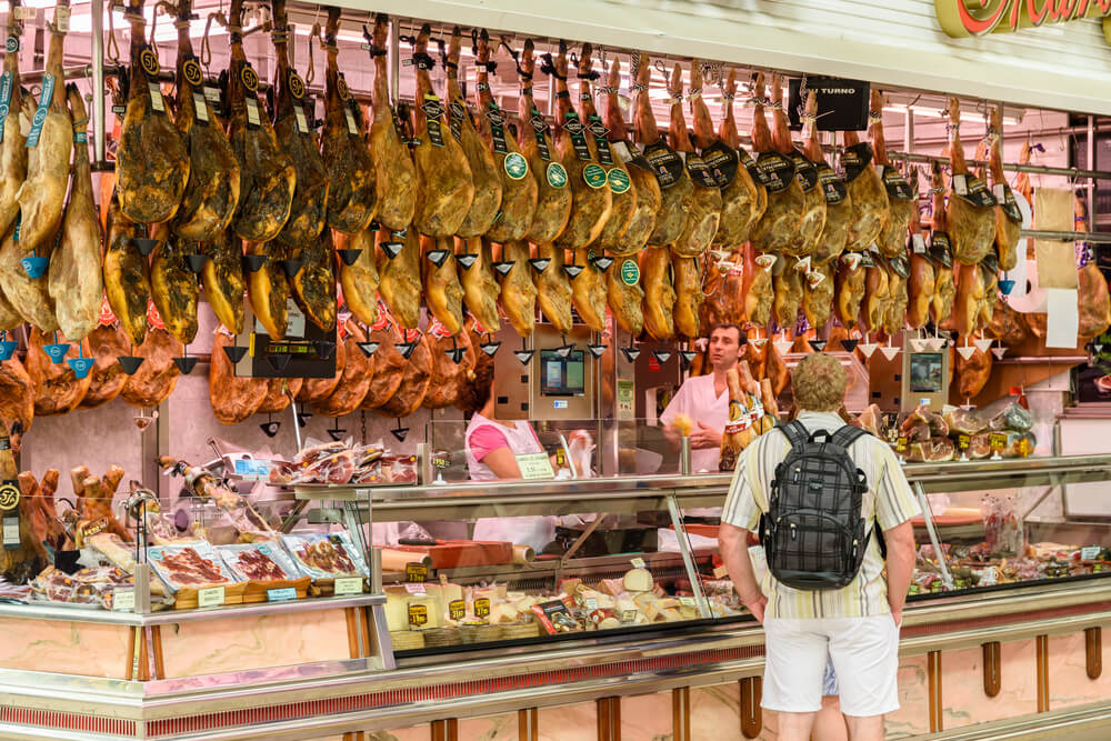 turista olha para os jamons num mercado tradicional