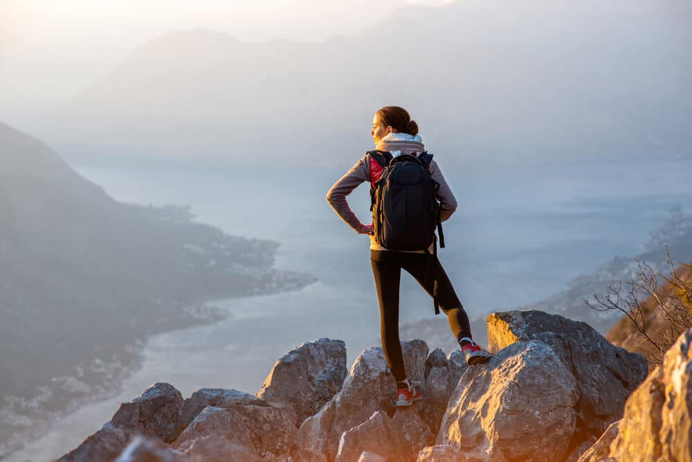 mulher no topo de uma montanha observa as vistas