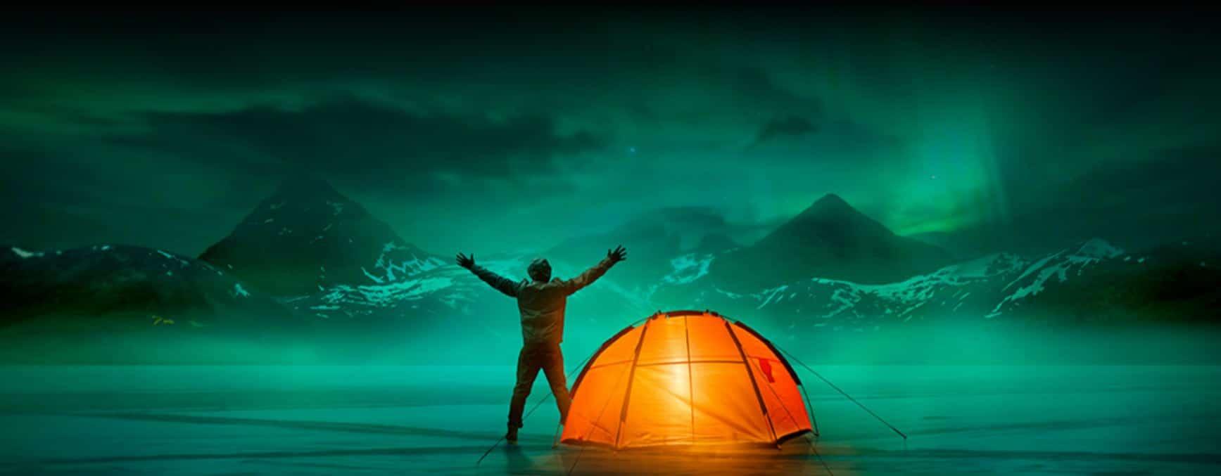 rapaz com tenda laranja ve as auroras boreais