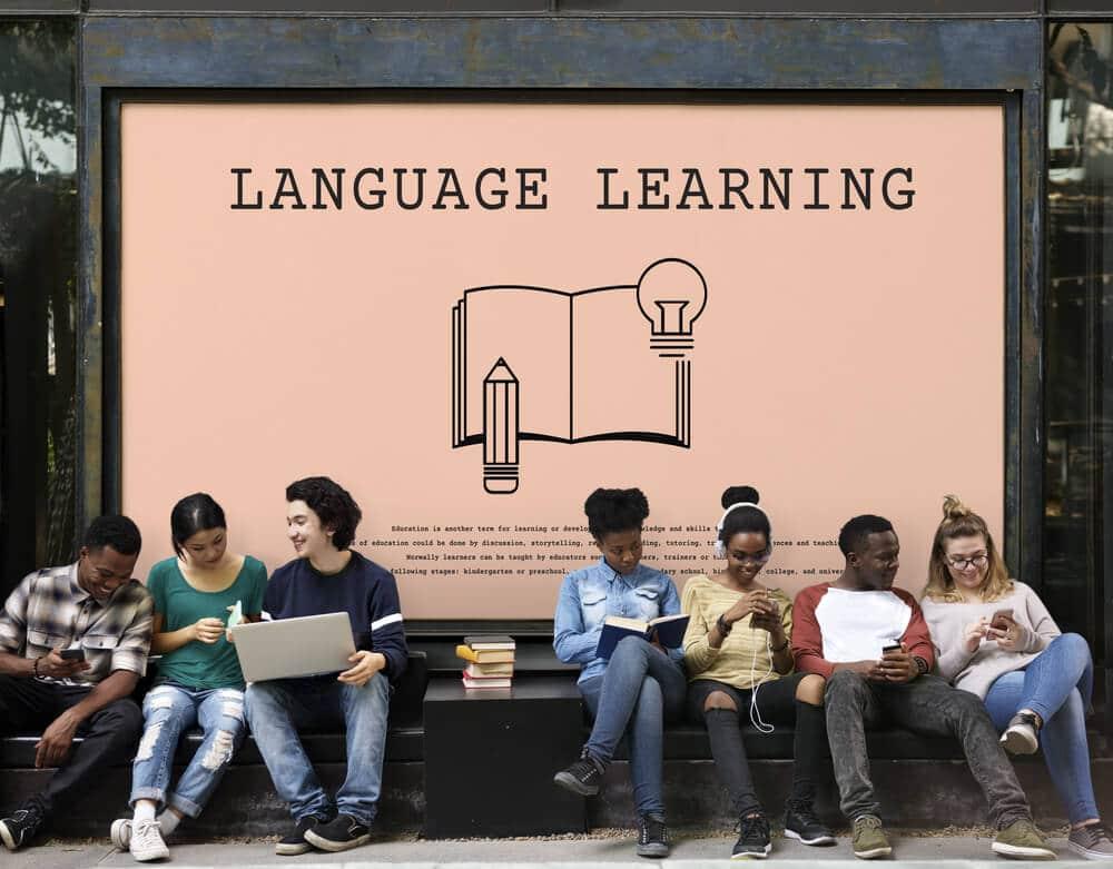 varios jovens sentados em frente a um placar sobre o ensino de linguas