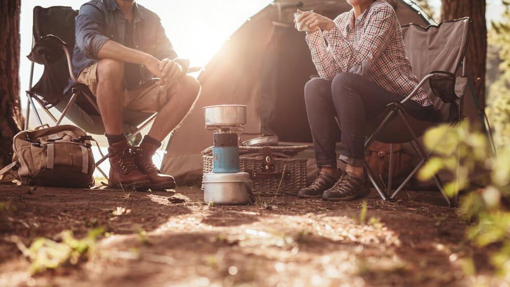 duas pessoas no campismo tomam cafe