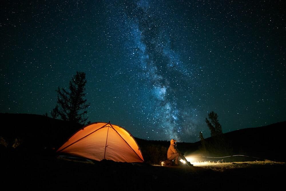 noite estrelada e tenda de campismo laranja