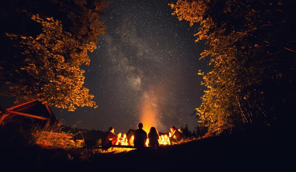 duas pessoas observam a via lactea desde à volta de uma fogueira