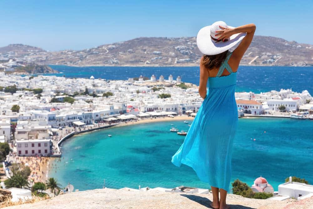 panoramica de mykonos e mulher de vestido azul