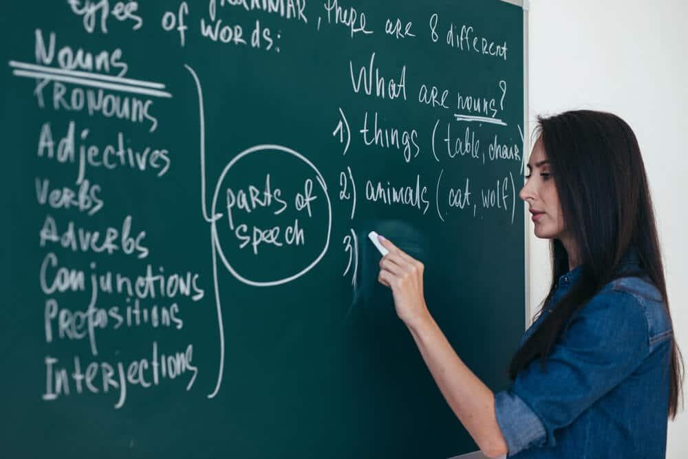 mulher escreve num quadro de giz