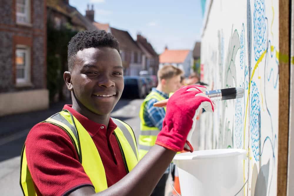 rapaz pinta uma casa