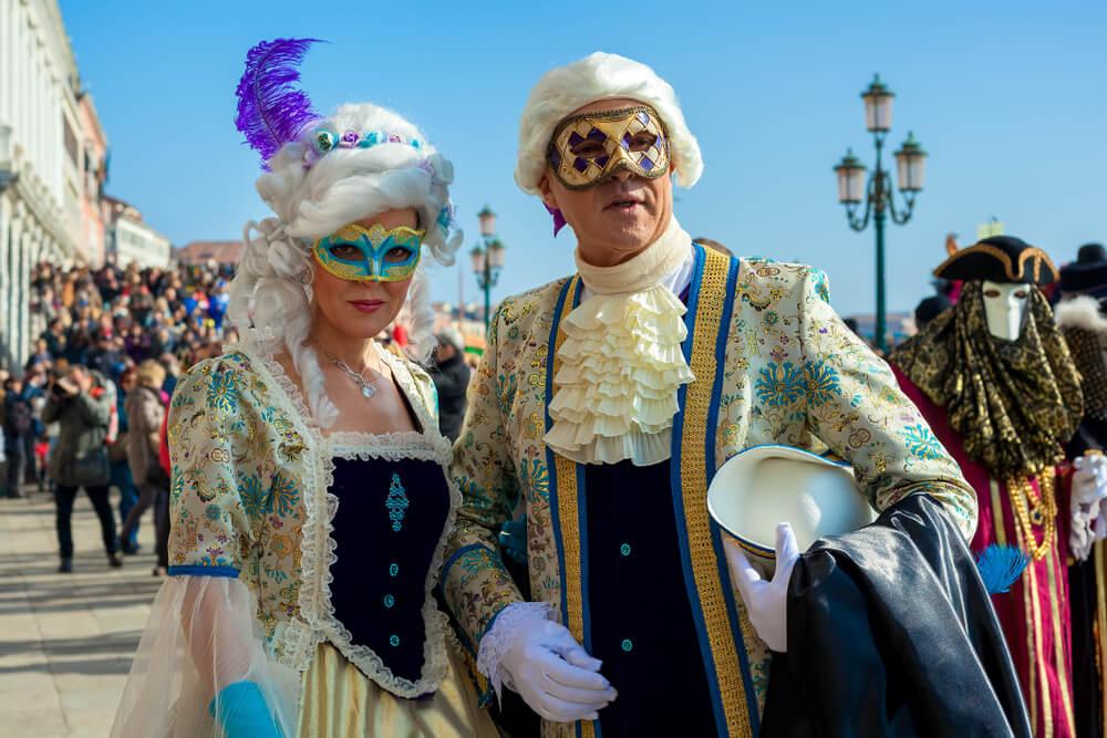 casal vestido com trajes e mascaras tipicos do carnaval de veneza