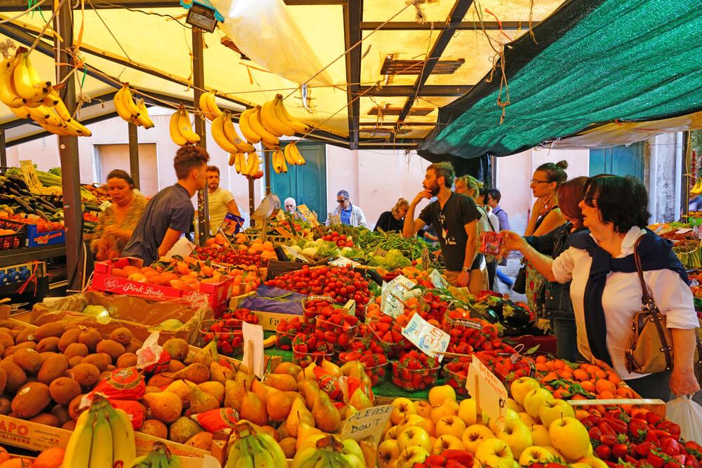 pessoas a comprar frutas numa banca do mercado