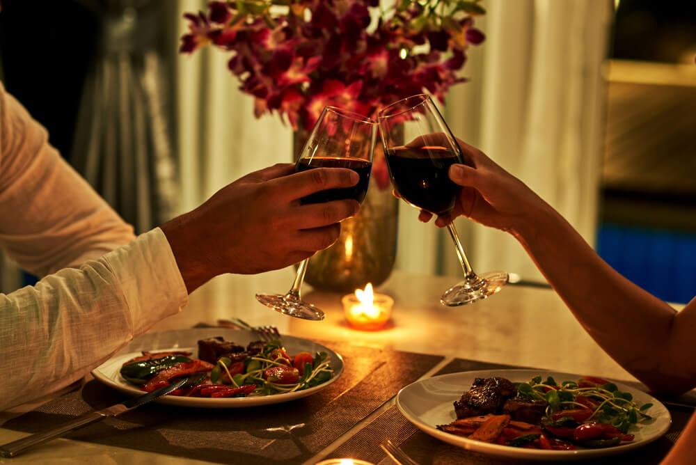casal brinda com copo de vinho num jantar romantico
