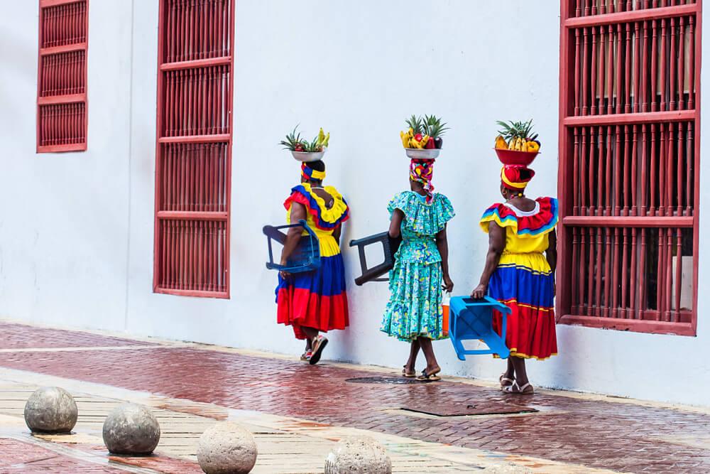 mulheres colombianas com fruta na cabeça e vestidos tradicionais