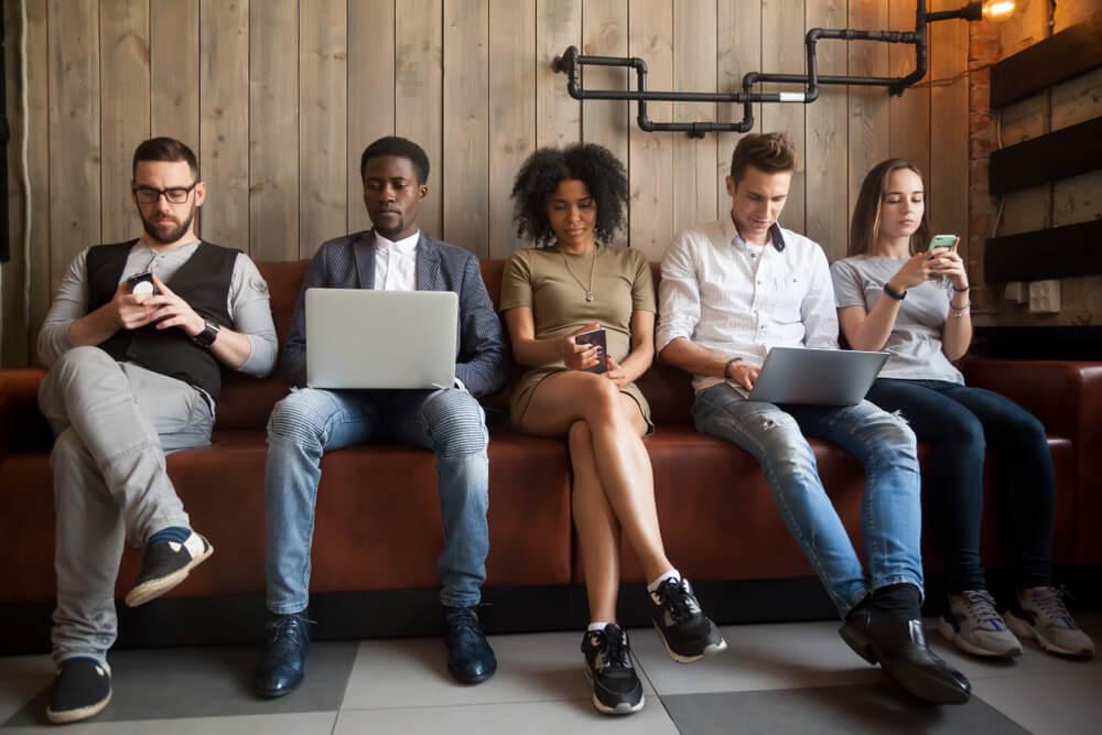 jovens sentados num banco a traballhar nos portateis