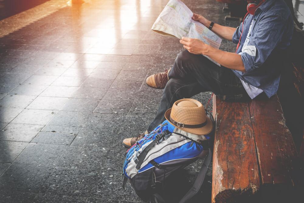 rapaz jovem sentado num banco com mochila ao lado