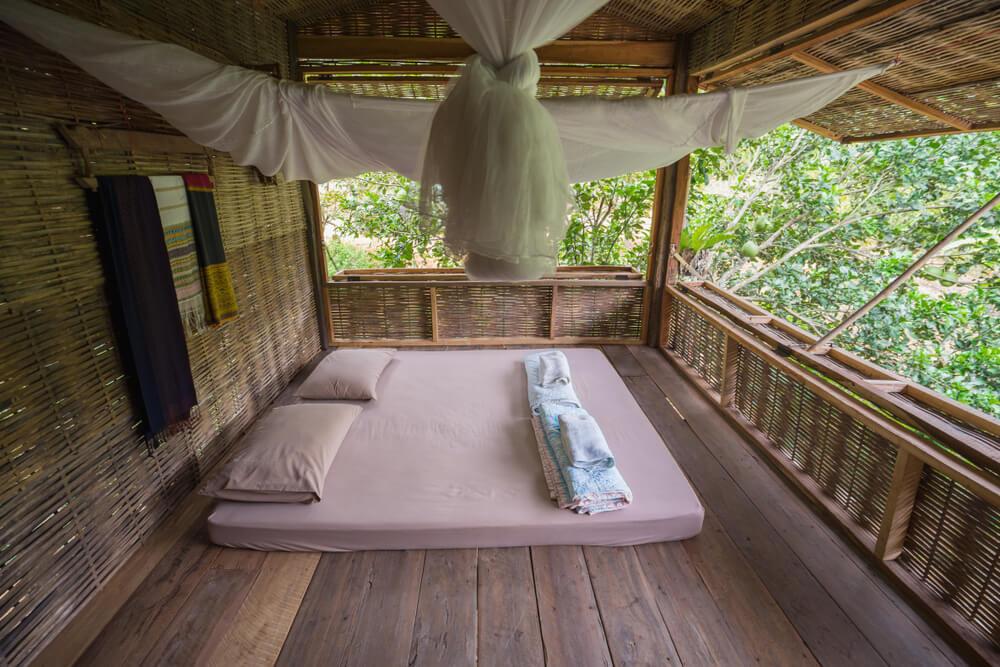 cama numa varanda com mosquiteiro