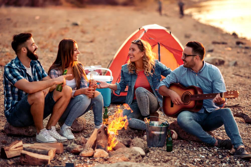 jovens sentados a volta de uma fogueira num campismo