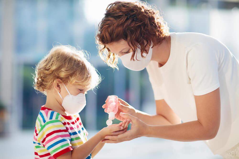 mae com mascara desinfecta as mãos do filho